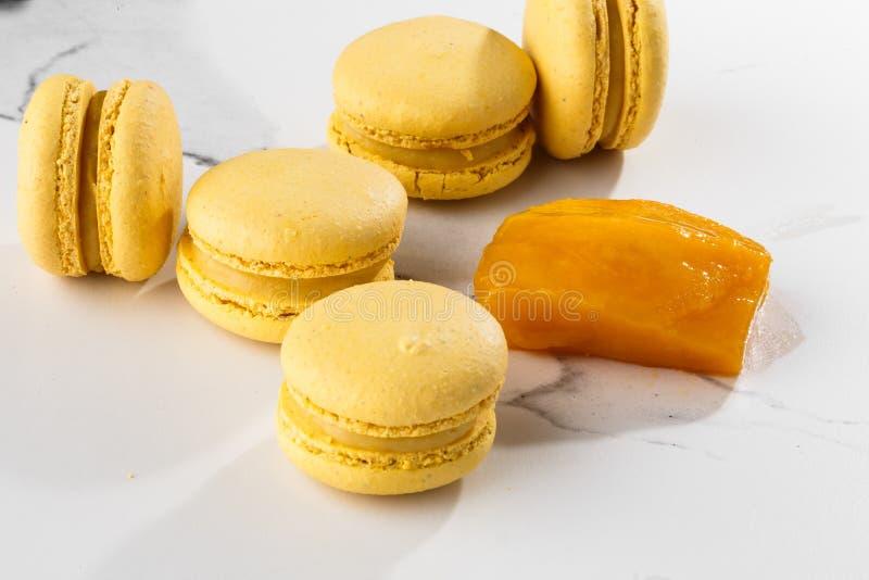 Französische Makronen lokalisierten Selektiver Fokus Schöne gelbe Makronen mit geschnittener Mango auf Marmorhintergrund stilvoll lizenzfreie stockfotografie