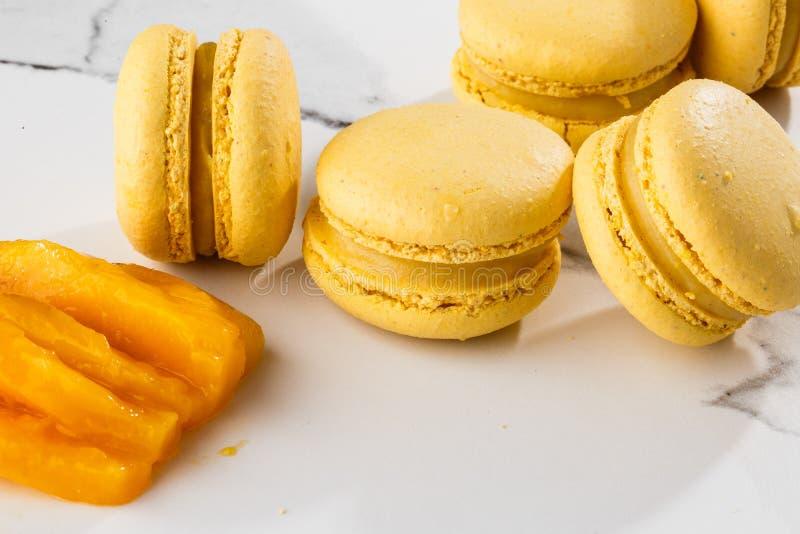 Französische Makronen lokalisierten Selektiver Fokus Schöne gelbe Makronen mit geschnittener Mango auf Marmorhintergrund stilvoll stockbilder
