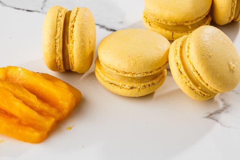 Französische Makronen lokalisierten Selektiver Fokus Schöne gelbe Makronen mit geschnittener Mango auf Marmorhintergrund stilvoll lizenzfreies stockbild