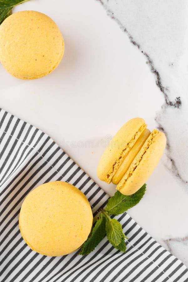 Französische Makronen lokalisierten Selektiver Fokus Schöne gelbe Makronen mit Minze in gestreifter Serviette auf Marmorhintergru lizenzfreie stockfotografie