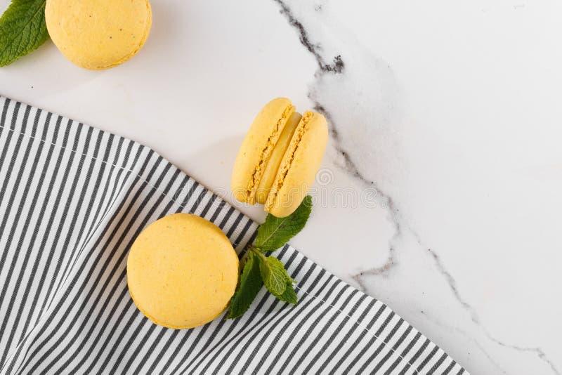 Französische Makronen lokalisierten Selektiver Fokus Schöne gelbe Makronen mit Minze in gestreifter Serviette auf Marmorhintergru lizenzfreie stockbilder