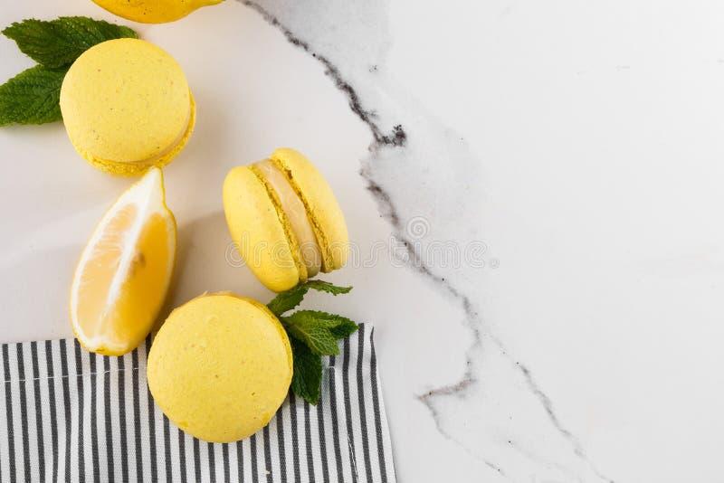 Französische Makronen lokalisierten Selektiver Fokus Schöne gelbe Makronen mit Minze und Zitrone in gestreifter Serviette auf Mar stockfotos
