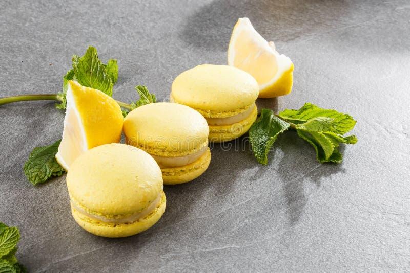 Französische Makronen lokalisierten Selektiver Fokus Schöne gelbe Makronen mit Zitrone und Minze auf grauem Steinhintergrund lizenzfreie stockbilder