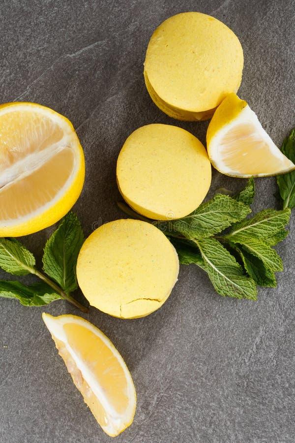 Französische Makronen lokalisierten Selektiver Fokus Schöne gelbe Makronen mit Zitrone und Minze auf grauem Steinhintergrund stockfotografie