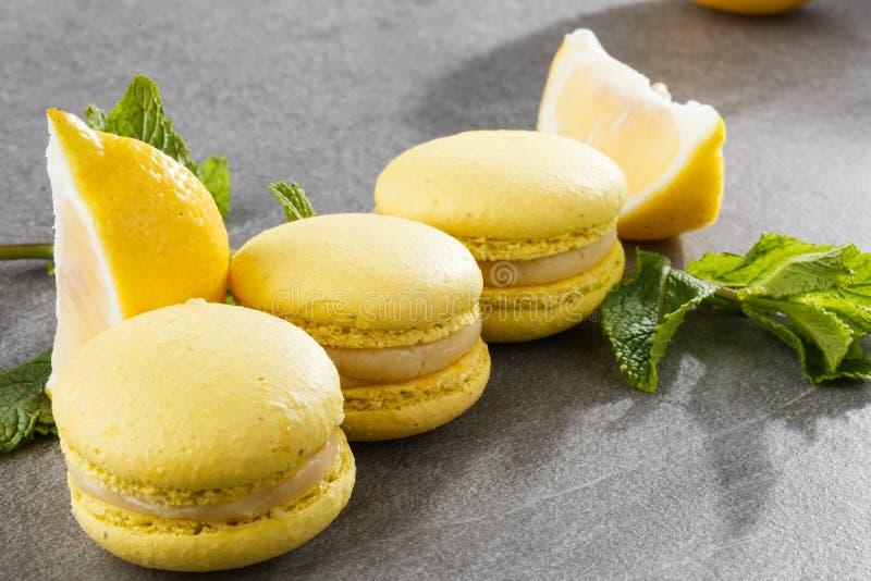Französische Makronen lokalisierten Selektiver Fokus Schöne gelbe Makronen mit Zitrone und Minze auf grauem Steinhintergrund lizenzfreie stockfotos