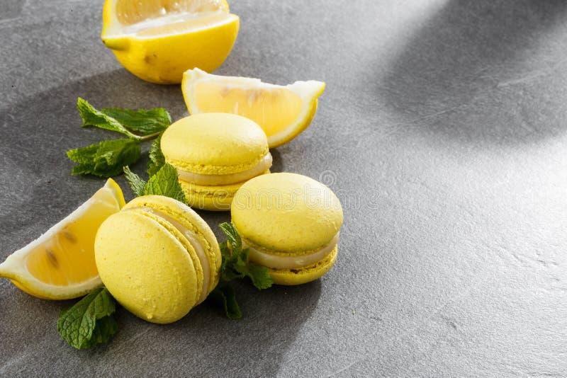 Französische Makronen lokalisierten Selektiver Fokus Schöne gelbe Makronen mit Zitrone und Minze auf grauem Steinhintergrund lizenzfreies stockbild
