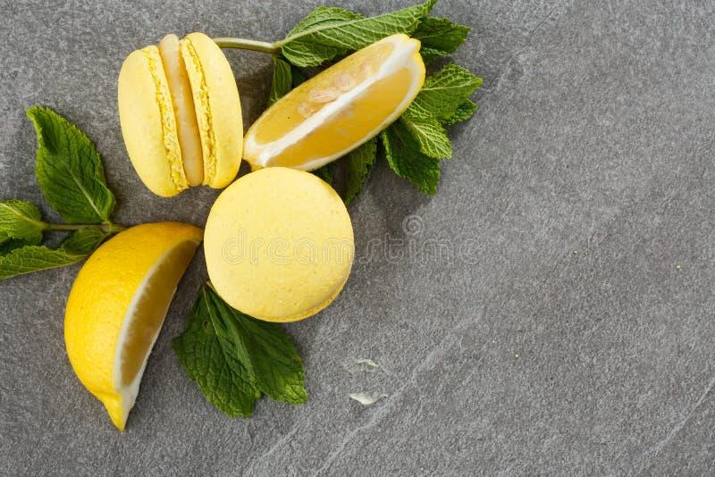 Französische Makronen lokalisierten Selektiver Fokus Schöne gelbe Makronen mit Zitrone und Minze auf grauem Steinhintergrund stockbild