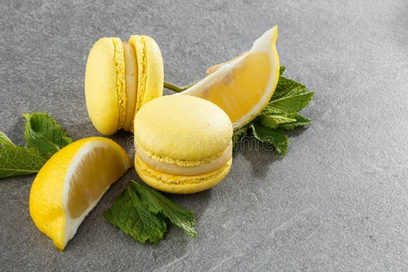 Französische Makronen lokalisierten Selektiver Fokus Schöne gelbe Makronen mit Zitrone und Minze auf grauem Steinhintergrund lizenzfreie stockfotografie
