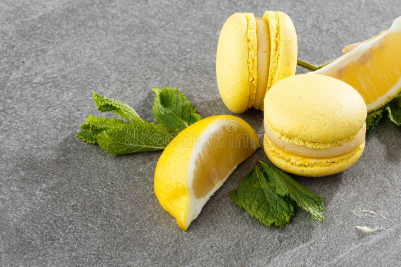 Französische Makronen lokalisierten Selektiver Fokus Schöne gelbe Makronen mit Zitrone und Minze auf grauem Steinhintergrund stockbilder