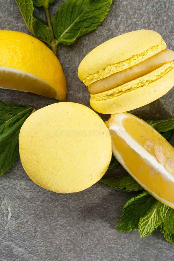 Französische Makronen lokalisierten Selektiver Fokus Schöne gelbe Makronen mit Zitrone und Minze auf grauem Steinhintergrund lizenzfreies stockfoto