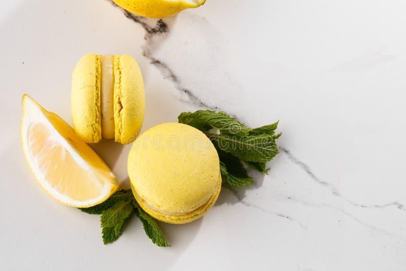 Französische Makronen lokalisierten Selektiver Fokus Schöne gelbe Makronen mit Zitrone und Minze auf Marmorhintergrund stilvoll lizenzfreies stockbild