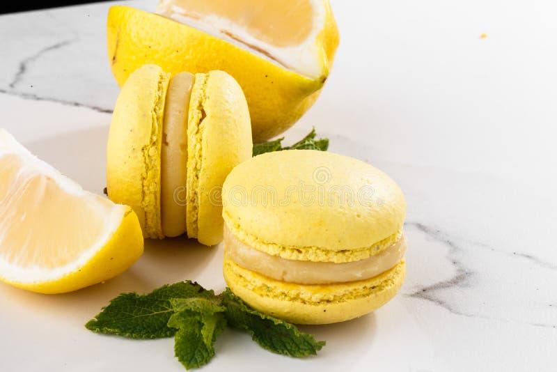Französische Makronen lokalisierten Selektiver Fokus Schöne gelbe Makronen mit Zitrone und Minze auf Marmorhintergrund stilvoll stockfotos
