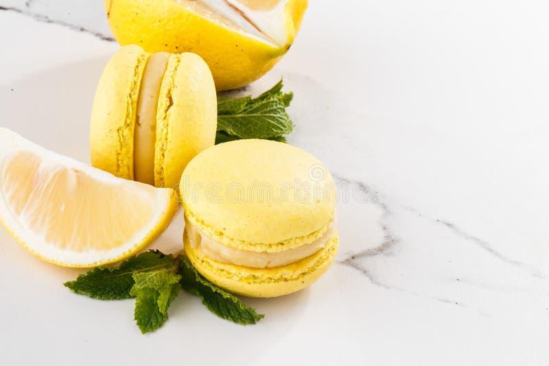 Französische Makronen lokalisierten Selektiver Fokus Schöne gelbe Makronen mit Zitrone und Minze auf Marmorhintergrund stilvoll lizenzfreie stockfotografie