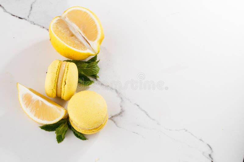Französische Makronen lokalisierten Selektiver Fokus Schöne gelbe Makronen mit Zitrone und Minze auf Marmorhintergrund stilvoll lizenzfreie stockfotos