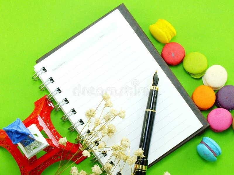 Französische Makronen mit Trockenblume und leerem Notizbuch paginieren Hintergrund lizenzfreies stockbild