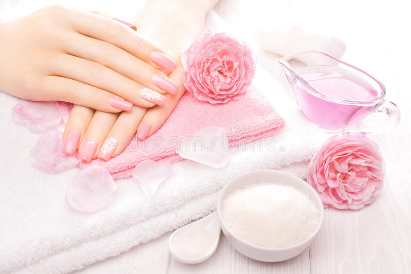 Französische Maniküre mit ätherischen Ölen, rosafarbene Blumen Badekurort lizenzfreies stockbild