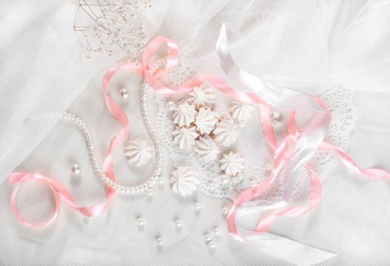 Französische Meringeplätzchen für Heiratshintergrund mit Perlen, rosa und weiße Satinbänder und Spitze, Ebenenlage stockbild