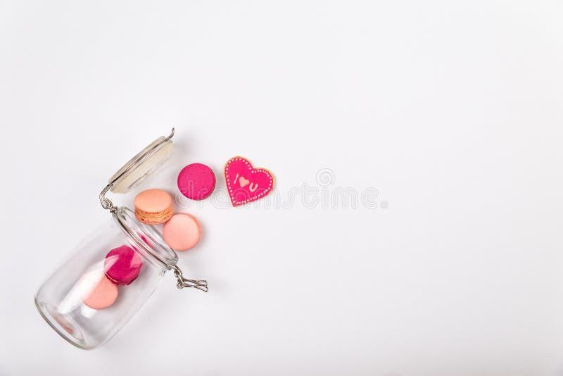 Französische rosa macarons oder Makronen und ich liebe dich Plätzchen, das aus einem Glasgefäß auf einem weißen Hintergrund mit c lizenzfreies stockbild