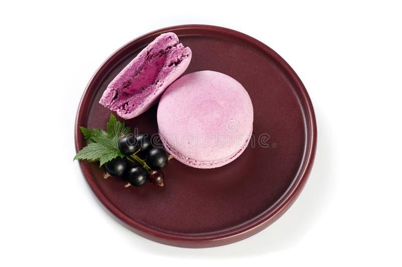 Französischer macaron der schwarzen Johannisbeere mit Sahne Käse, der auf Weinplatte füllt Getrennt auf wei?em Hintergrund lizenzfreies stockbild