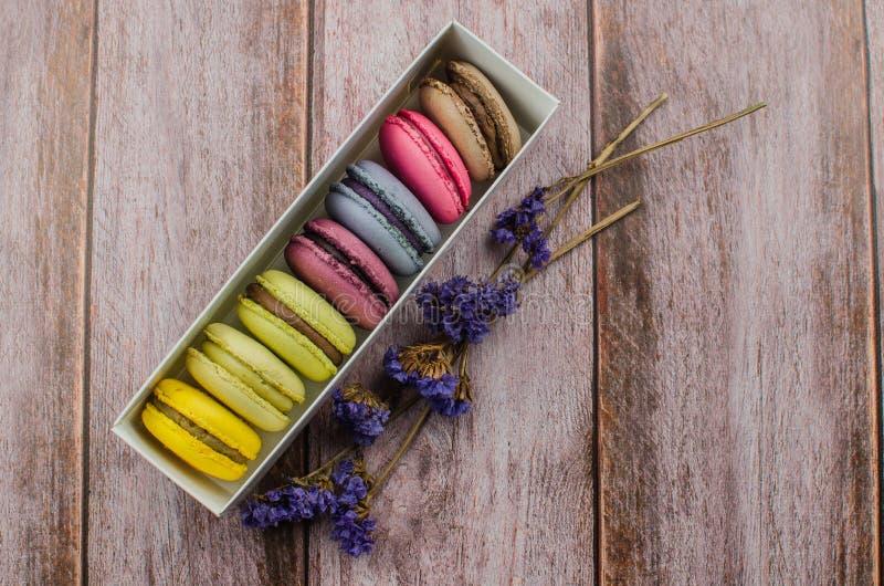 Französischer Makronenkuchen Makronen im Kasten mit Trockenblumen auf hölzernem Hintergrund stockfotografie