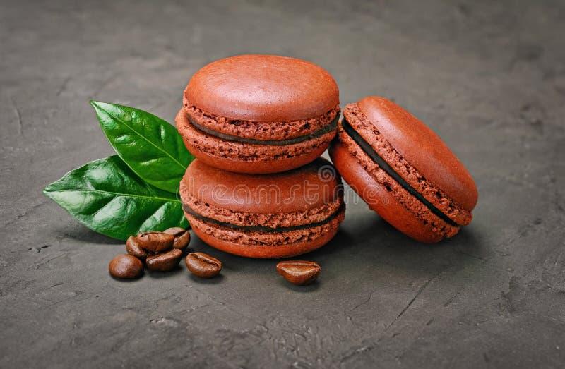 Französischer Schokoladenfondantpudding Süße braune Schokolade Makronen oder macarons mit Kaffeearoma und -bohnen lizenzfreies stockfoto