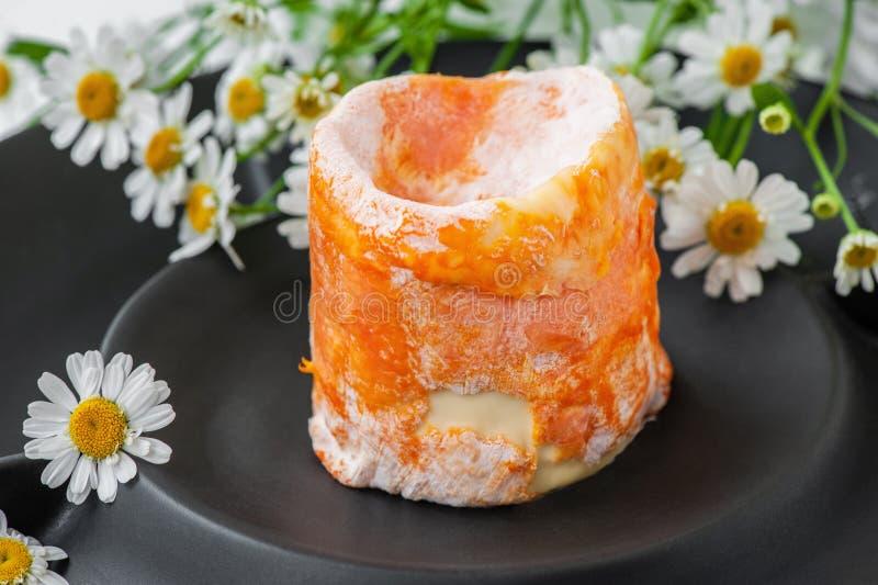 Französischer Weichkäse mit weißen epoisses orange Rinde der Form auf einer schwarzen Mattplatte Abschluss oben stockbild