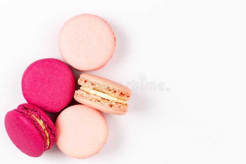 Französisches Rosa und magentarote macarons oder Makronen, Draufsicht über einen weißen Hintergrund mit copyspace stockbild
