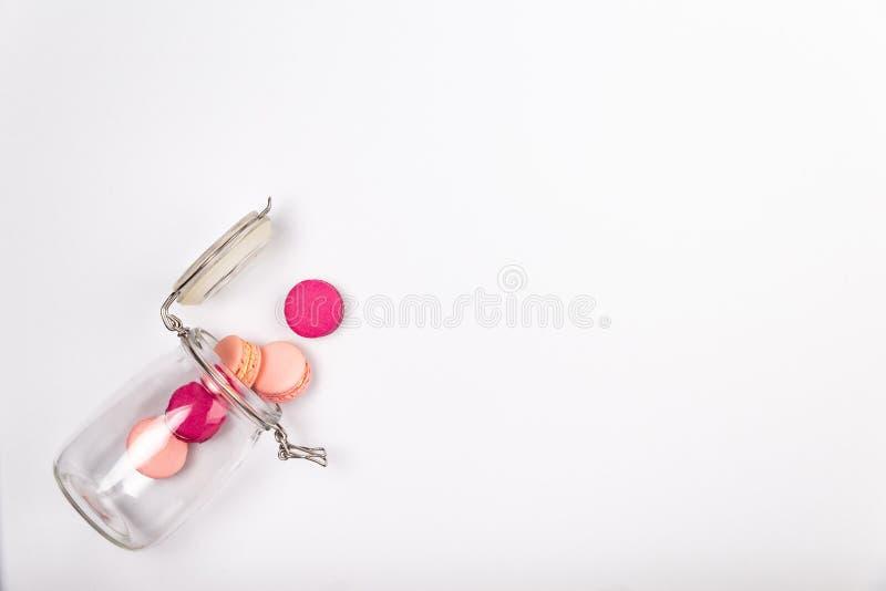 Französisches Rosa und magentarote macarons oder Makronen, fallend aus einem Glasgefäß auf einem weißen Hintergrund mit copyspace stockfoto