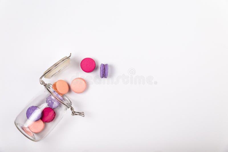 Französisches Rosa und purpurrote macarons oder Makronen, fallend aus einem Glasgefäß auf einem weißen Hintergrund mit copyspace  stockbilder