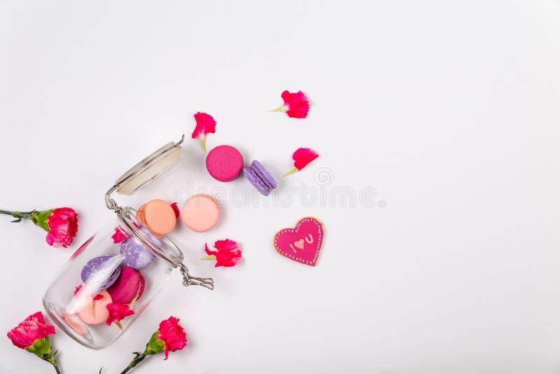 Französisches Rosa und purpurrote Makronen, ich liebe dich Plätzchen und rosa Inkarnationsblumen, die aus einem Glasgefäß auf wei stockfoto