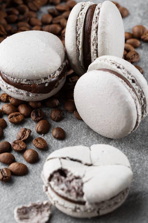 Franz?sische Makronen mit Kaffeebohnen Selektiver Fokus Makrone im grauen Ton Französische Abbruch macarons auf grauem Stein stockfotografie