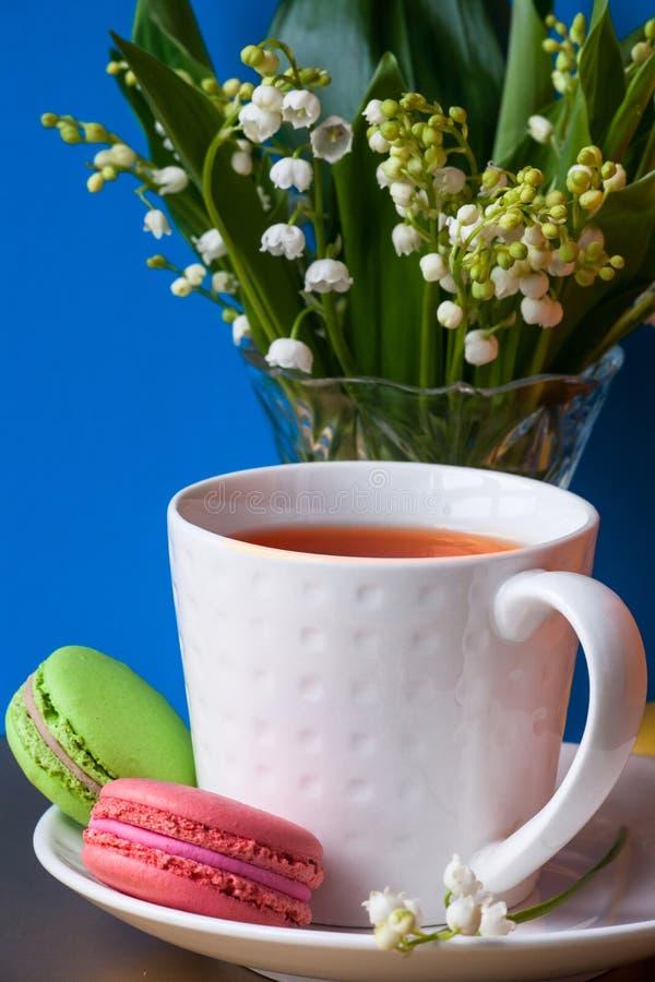 Franz?sische mehrfarbige Kuchen macarons und eine Tasse Tee Ein Blumenstrauß des Maiglöckchens in einem Kristallvase lizenzfreie stockbilder