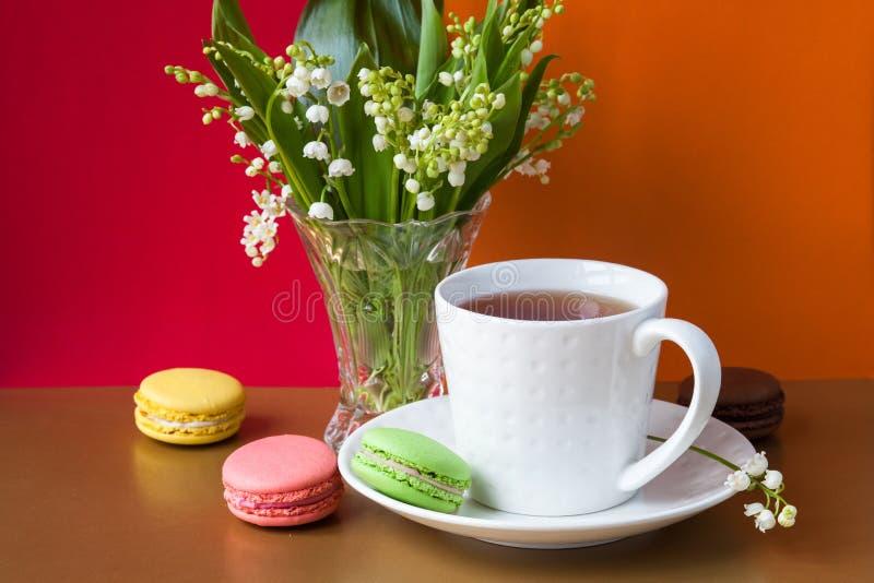 Franz?sische mehrfarbige Kuchen macarons und eine Tasse Tee Ein Blumenstrau? des Maigl?ckchens in einem Kristallvase stockbilder