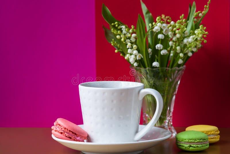 Franz?sische mehrfarbige Kuchen macarons und eine Tasse Tee Ein Blumenstrau? des Maigl?ckchens in einem Kristallvase lizenzfreies stockfoto