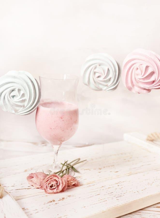 Frappé della frutta, dessert dolci della meringa e fiori teneri su un vassoio grezzo di legno natura morta tenera leggera fotografia stock libera da diritti