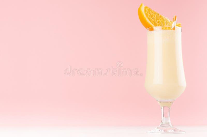 Frappé luminoso delle arance in vetro di eleganza con le fette arancio sulla tavola di legno bianca e sulla parete rosa-chiaro pa fotografia stock libera da diritti