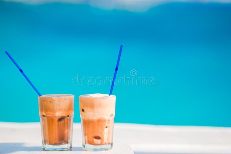 Frappe,在海滩的冰冻咖啡 夏天冰了咖啡frappuccino、frappe或者拿铁在高玻璃背景中海  免版税库存照片