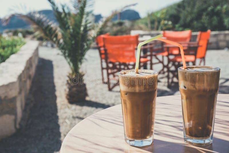 Frappe кофе, греческая кухня на таблице на пляже стоковые фотографии rf