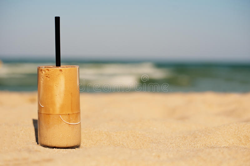 Frappe, ice coffee on the beach. Summer iced coffee (frappuccino, frappe or latte) in a tall glass. On sand background - beach bar holiday cold beverages menu stock photo