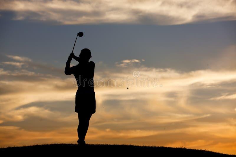 Frapper la boule de golf au coucher du soleil. photographie stock