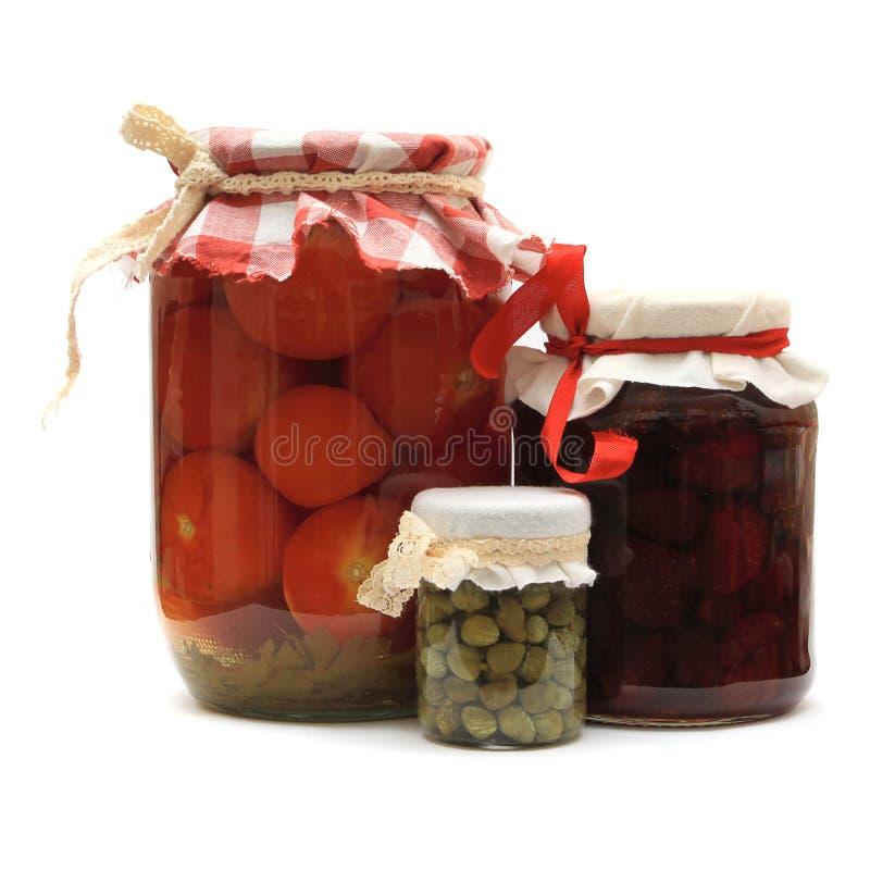 Frasco com conservas. Atolamento, tomates conservados, alcaparras fotografia de stock royalty free