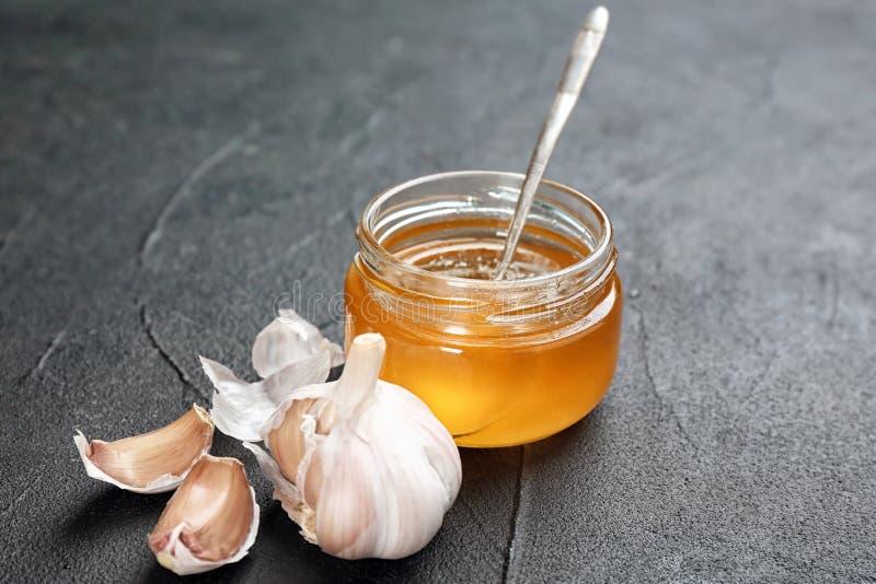Frasco com mel e alho para o frio fotografia de stock