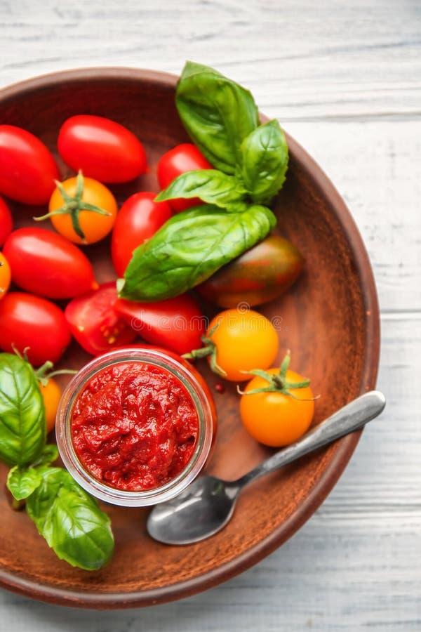 Frasco com pasta de tomate e os legumes frescos na placa, close up fotografia de stock