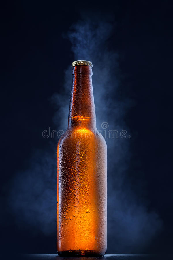 Frasco de cerveja fria com gotas no preto foto de stock royalty free