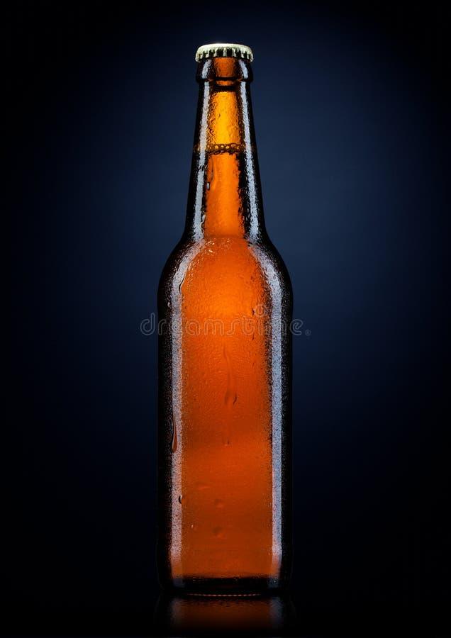Frasco de cerveja fria com gotas, no preto fotos de stock
