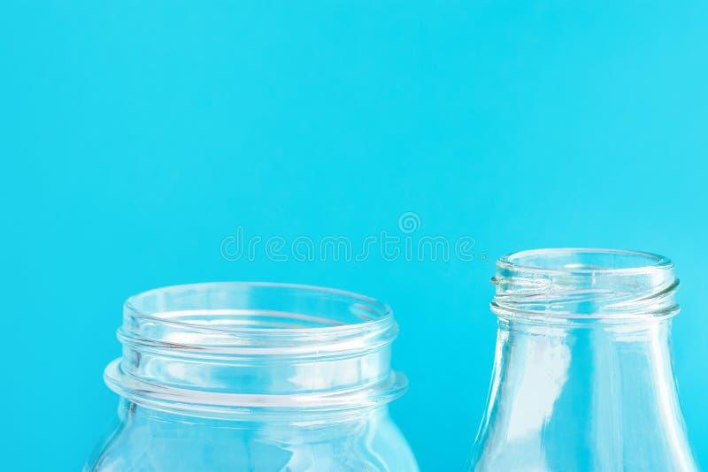 Frasco de cristal da garrafa dos produtos vidreiros em claro - fundo azul Desperdício zero das alternativas plástico-livres reusá fotos de stock