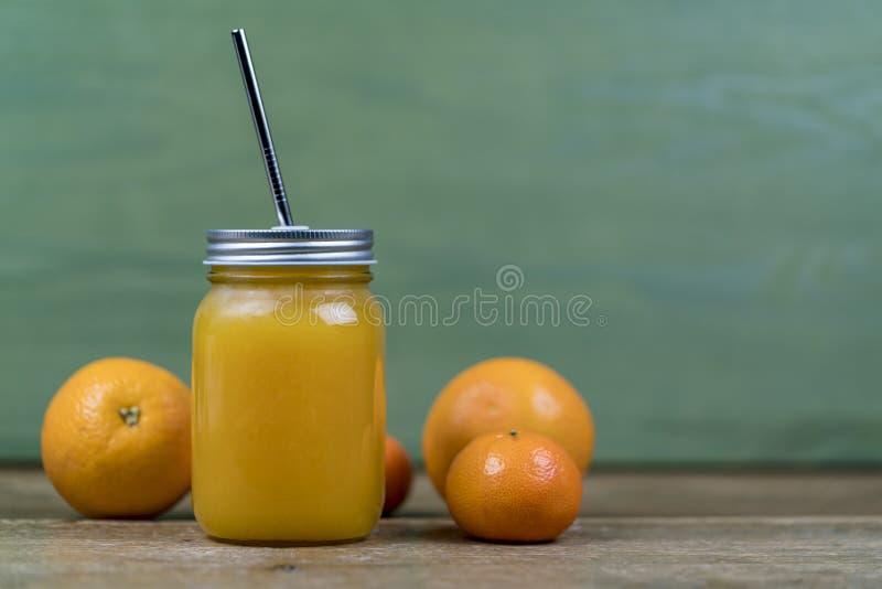 Frasco de pedreiro com suco de laranja e uma palha foto de stock