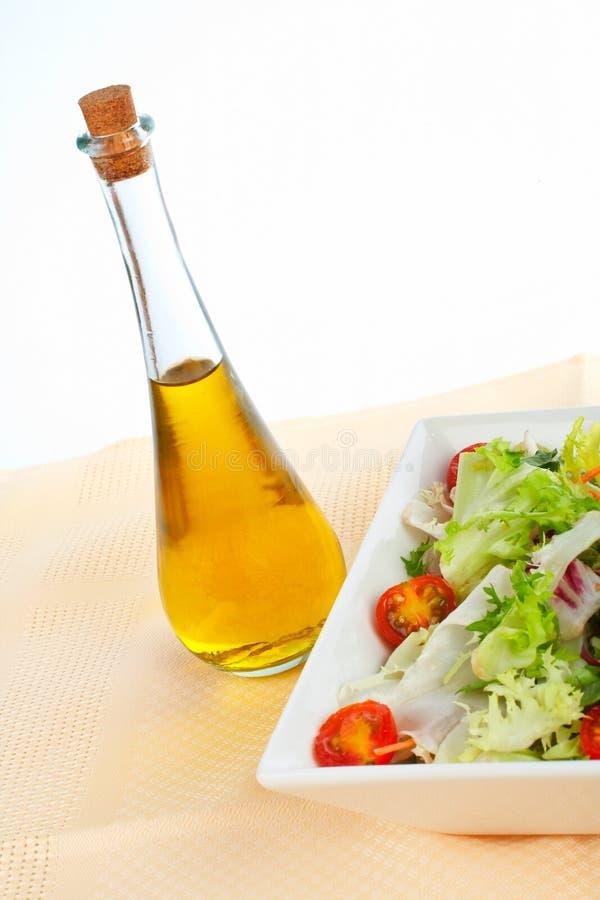 Frasco de petróleo e salada verde imagens de stock