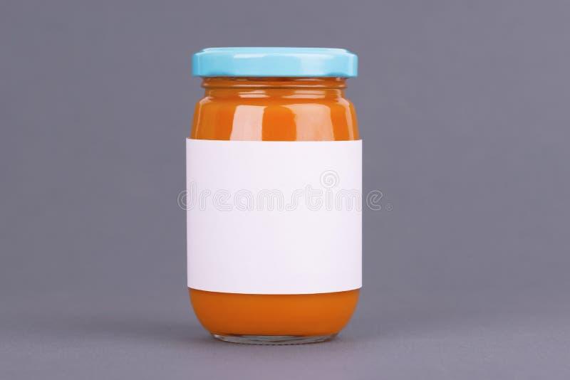 Frasco de vidro alaranjado para o banco do comida para bebê no fundo cinzento Puré orgânico do comida para bebê Zombaria acima se fotografia de stock