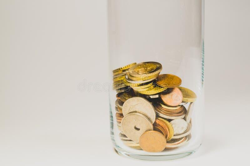 Frasco de vidro com as moedas internacionais dos vários países conceito do armazenamento da finança imagem de stock